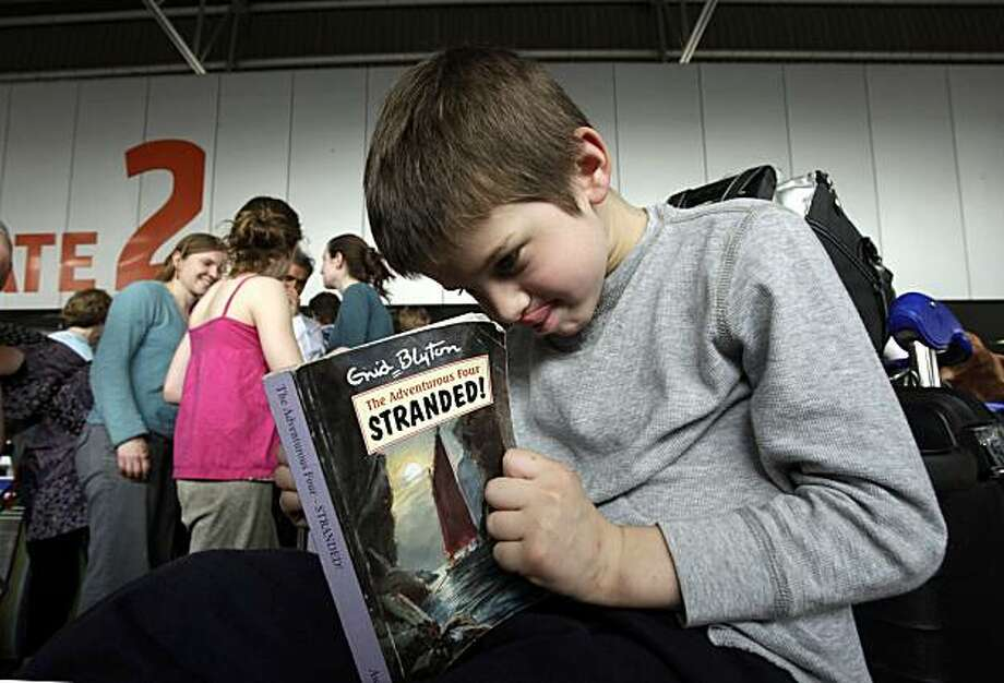 "Tom Sandford Bondy reads a book titled ""Stranded"" as he waits in line with other members of his family to try and board a Virgin Atlantic flight for London, at the Indira Gandhi International Airport, in New Delhi, India, Thursday, April 22, 2010. The weeklong airspace closures caused by the ash threat to aircraft represented the worst breakdown in civil aviation in Europe since World War II. This led to the cancellations of more than 100,000 flights, with airlines on track to lose over $2 billion. Photo: Gurinder Osan, AP"