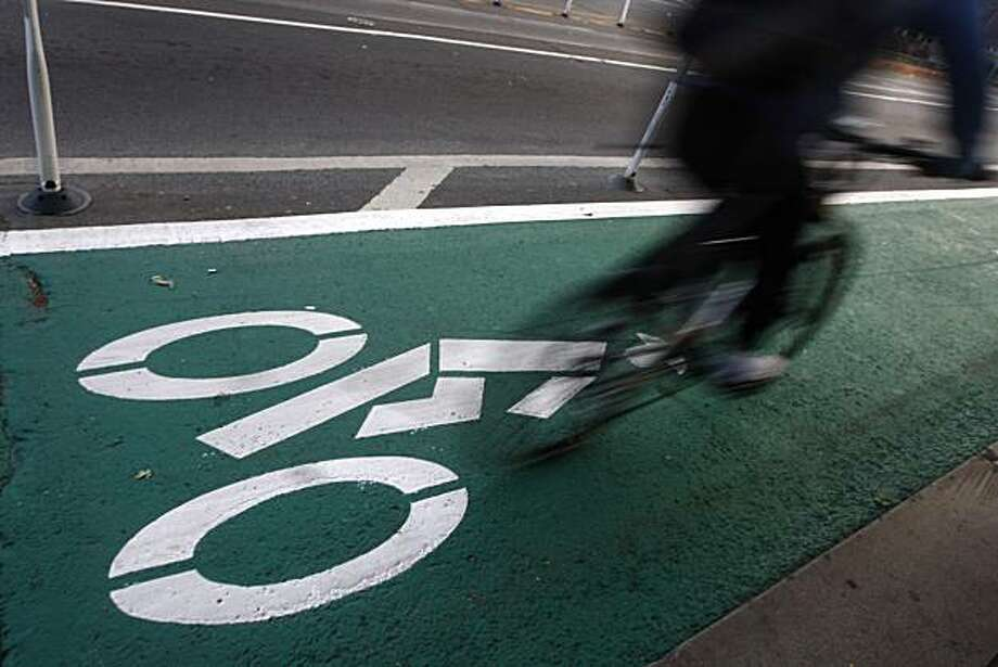 A bicyclist cruises down Market Street in bike lanes recently painted green on Bike to Work Day in San Francisco, Calif., on Thursday, May 13, 2010. Photo: Paul Chinn, The Chronicle