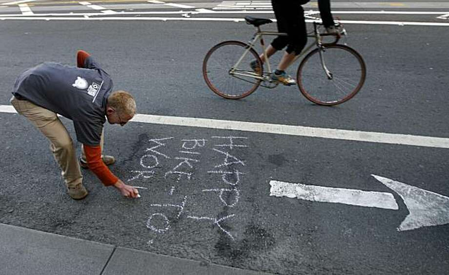 Robin Levitt scrawls a message in chalk in the bike lane on Market Street on Bike to Work Day in San Francisco, Calif., on Thursday, May 13, 2010. Photo: Paul Chinn, The Chronicle