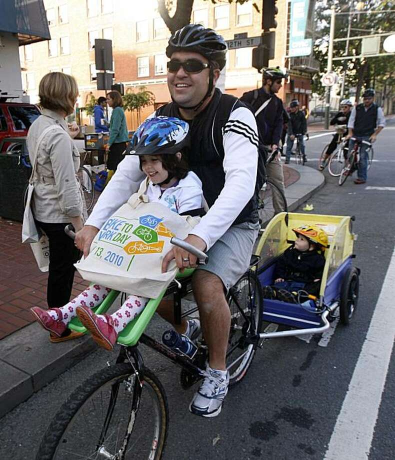 Sam Lopez was commuting from 16th and Mission streets to the Ferry Builing with his daughter California (front) and son Rio, in tow, when they stopped for refreshments at 12th and Market streets on Bike to Work Day in San Francisco, Calif., on Thursday, May 13, 2010. Photo: Paul Chinn, The Chronicle
