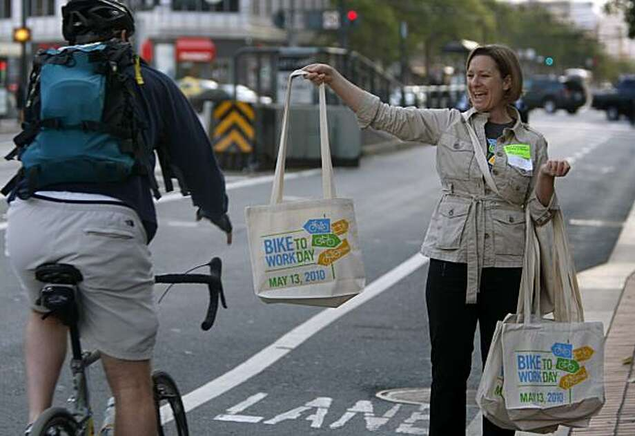 Cheryl Brinkman hands out tote bags to bicyclists riding past an energizing station at 12th and Market streets on Bike to Work Day in San Francisco, Calif., on Thursday, May 13, 2010. Photo: Paul Chinn, The Chronicle