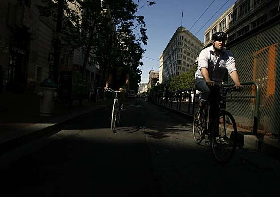 A bicyclist is illuminated by early morning light as he cycles down Market Street during Bike to Work day in San Francisco, Calif., on Thursday, May 14, 2009. Photo: Hardy Wilson, The Chronicle