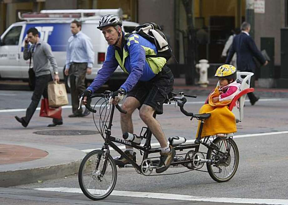 On the 15th annual Bay Area Bike to Work day, John Trevithick pedals his daughter Zoe Trevethick to daycare. Photo: Mike Kepka, The Chronicle