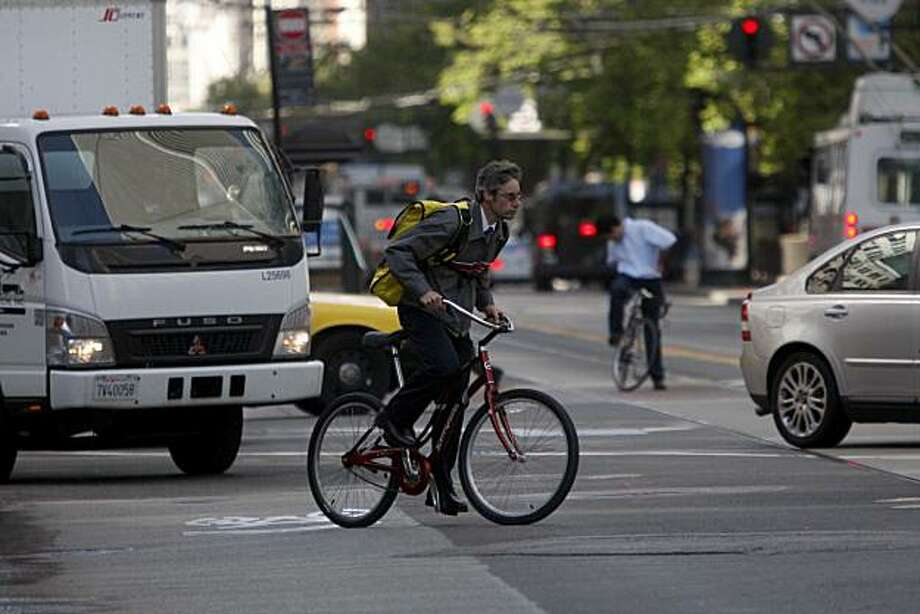 A local business man darts across Market Street during the 15th annual Bay Area Bike to Work day. Photo: Mike Kepka, The Chronicle