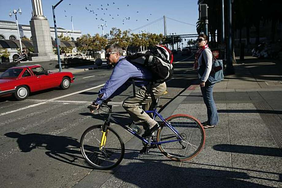 Willy Dommen, of San Anselmo, crosses over the Embracadero on his way to the ferry on Wednesday, October 8, 2008 in San Francisco, Calif. Dommen regularly bikes to work on his commute. San Francisco Superior Ross Mirkarimi has introduced a proposal to give people a tax break for biking to work. Photo: Lea Suzuki, The Chronicle