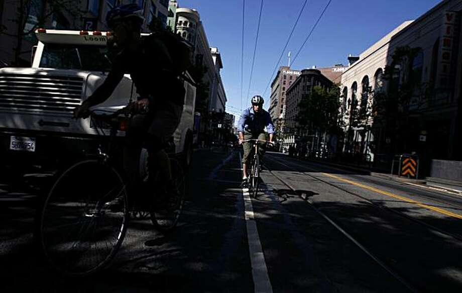 A bicyclist is illuminated by early morning light as he cycles down Market Street during Bike to Work day in San Francisco. Photo: Hardy Wilson, The Chronicle