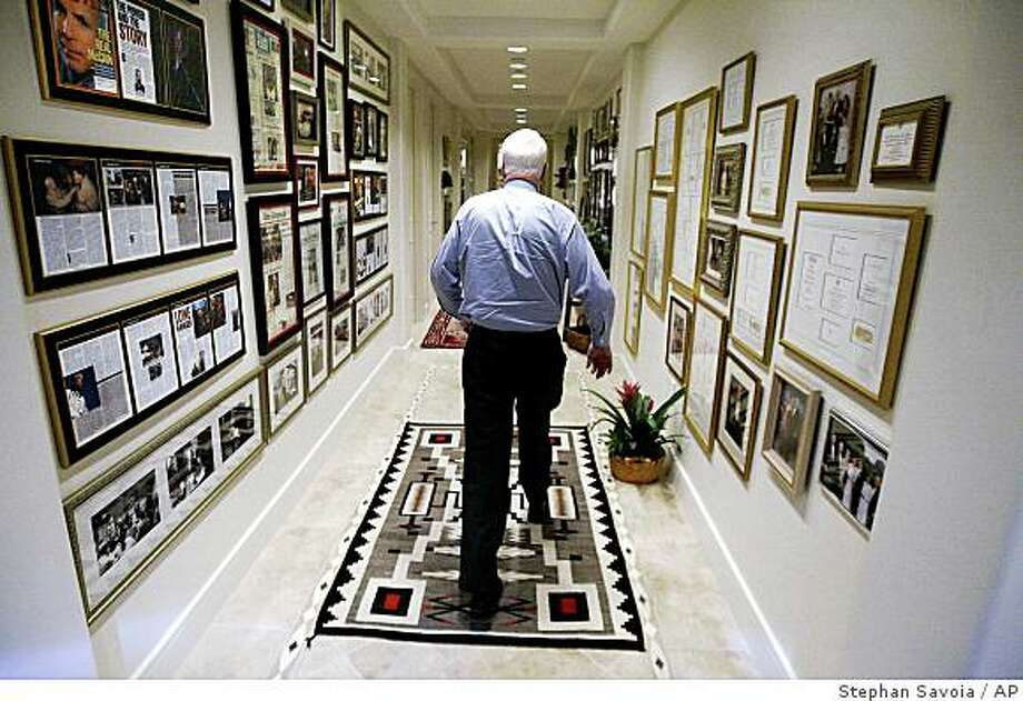 Republican presidential candidate Sen. John McCain, R-Ariz., walks down a hallway in his home lined with photographs and news clippings of his career in Phoenix, Ariz. on Feb. 5, 2008. Photo: Stephan Savoia, AP