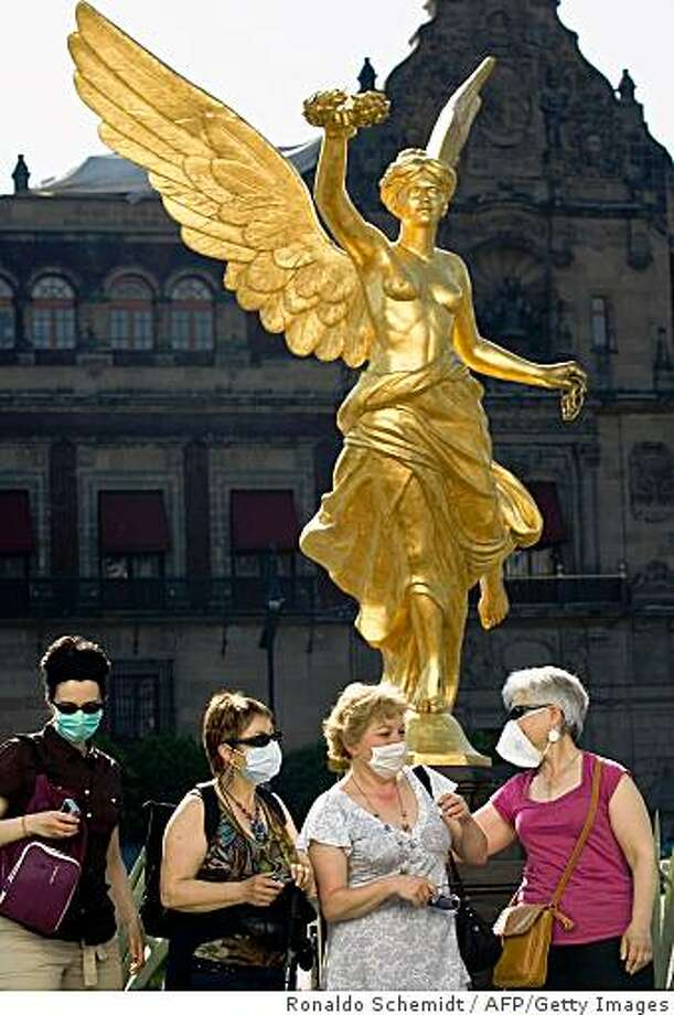 "French tourists chat at Zocalo Square in Mexico City, on April 28, 2009. As a preventive measure against contagion of the deadly swine flu virus, more than 500 cultural and athletic events --including mass celebration-- have been scuttled by government order in the capital city alone, as authorities banned large gatherings for at least 10 days. The swine flu virus that has killed dozens in Mexico could mutate into a ""more dangerous"" strain, Keiji Fukuda, acting WHO assistant-general for health, security and the environment said, adding that the UN agency will decide on Tuesday if it should raise its pandemic alert rating. Photo: Ronaldo Schemidt, AFP/Getty Images"