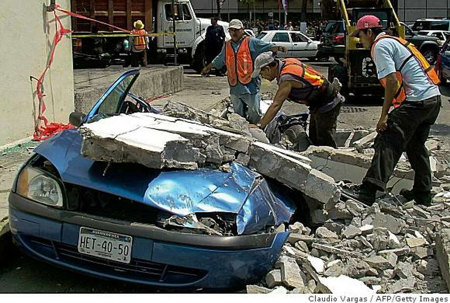 Local workers try to remove the debris of a wall that fell over a car in Acapulco, Guerrero state, after a 6.0-magnitude earthquake with the epicenter in Chilpancingo, in Mexico, on April 27, 2009. The quake shook buildings in Mexico City Monday, as the city grapples with an outbreak of deadly swine flu. AFP PHOTO/Claudio Vargas (Photo credit should read CLAUDIO VARGAS/AFP/Getty Images) Photo: Claudio Vargas, AFP/Getty Images