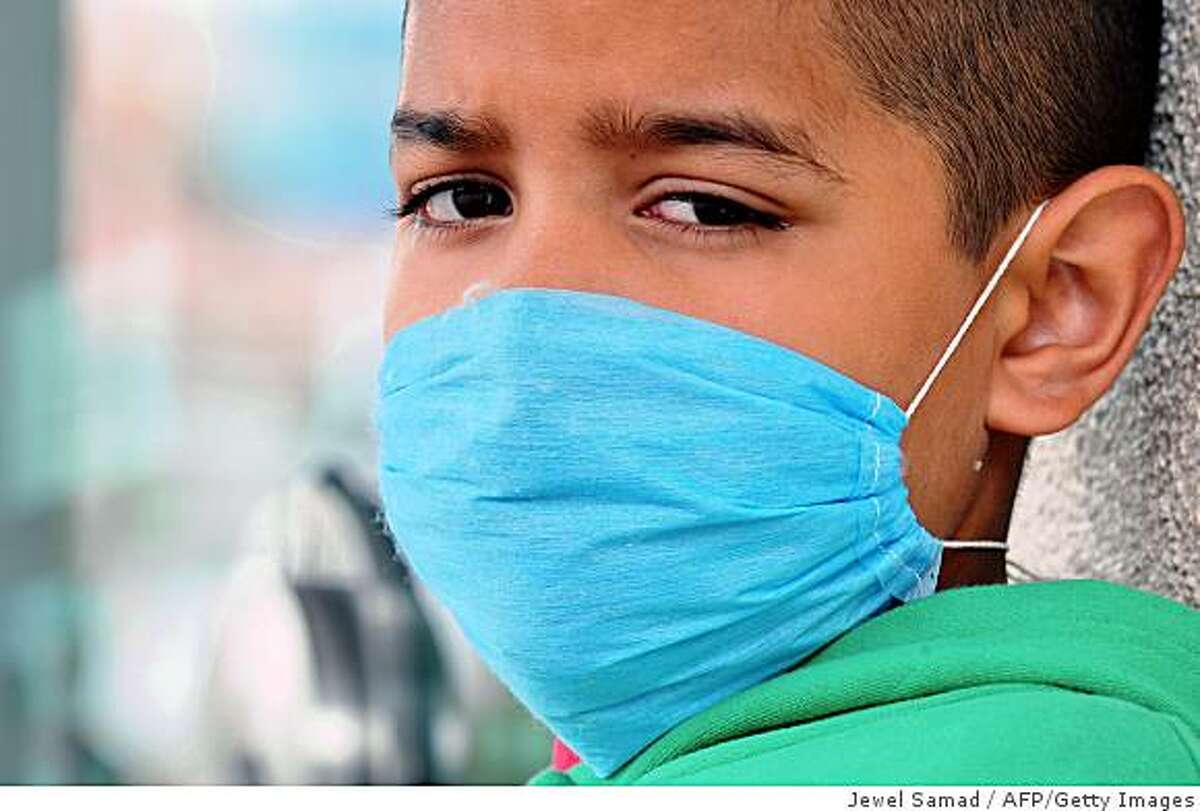 A boy, wearing a protective mask, waits at a bus stop crossing the international border between US and Mexico in San Ysidro, California, on April 27, 2009 with his family. So far the only swine flu deaths have been recorded in Mexico, where the probable toll rose Monday to 149, with 20 people confirmed to have died from the disease. The United States has recorded the second highest rate of infection, and officials doubled the number of confirmed US cases to 40 in five states. The World Health Organization (WHO) raised its flu pandemic alert level from three to four, signalling a
