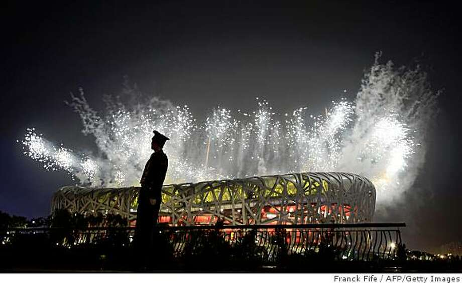 "A Chinese security personnel stands guard as fireworks display light up above the National Stadium also known as the ""Bird's Nest"" during the closing ceremony of the 2008 Beijing Olympic Games on August 24, 2008. Photo: Franck Fife, AFP/Getty Images"