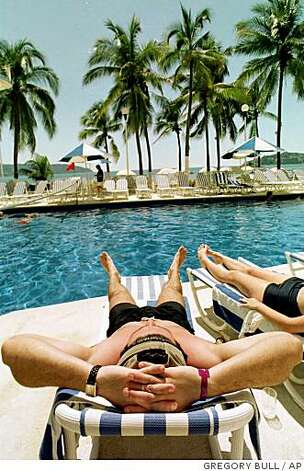 Tourists relax by the pool at a seaside resort in Acapulco, Mexico, ...