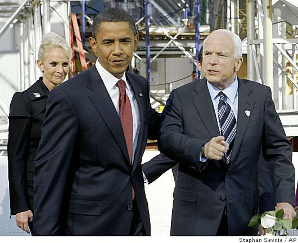 Republican presidential candidate, Sen., John McCain, R-Ariz., and Democratic presidential candidate, Sen., Barack Obama, D-Ill., talk as they walk together after participating in a Ground Zero 9/11 memorial observance Thursday, Sept. 11, 2008 in New York. McCain's wife Cindy, left, looks on. (AP Photo/Stephan Savoia)