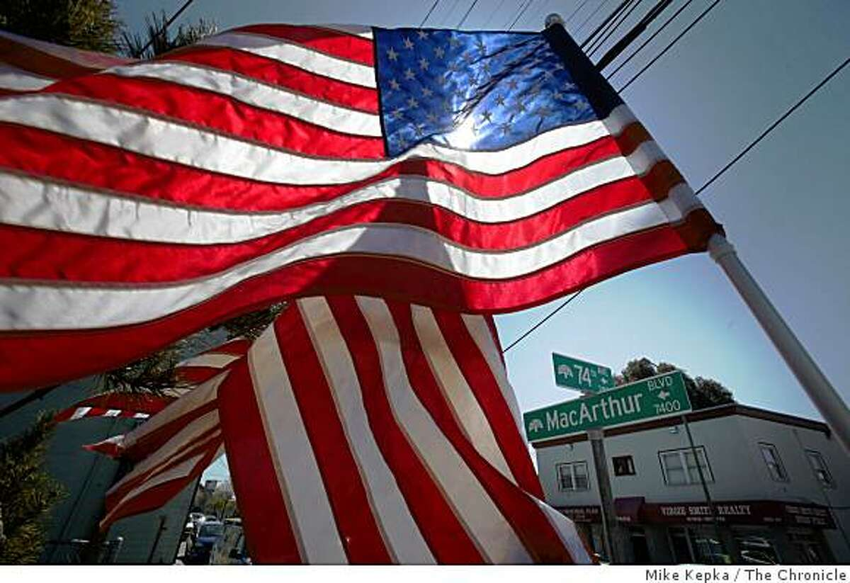 Two day after shots left an Oakland man and 4 Oakland Police officers dead, American flags flap in the breeze at the site of the incident on Monday March 23, 2009 in Oakland, Calif.
