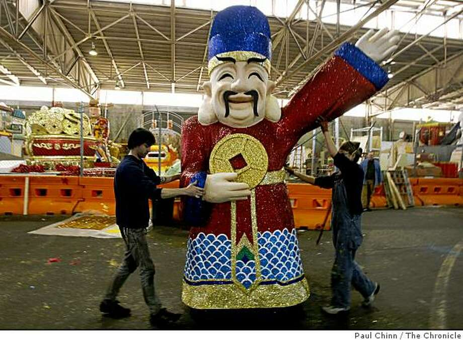 Kristofer Hammes (left) and Allison Lowe roll the Lord of Fortune through Pier 27 to mount it on a float for this weekend's Chinese New Year Parade in San Francisco, Calif., on Tuesday, Feb. 3, 2009. Photo: Paul Chinn, The Chronicle