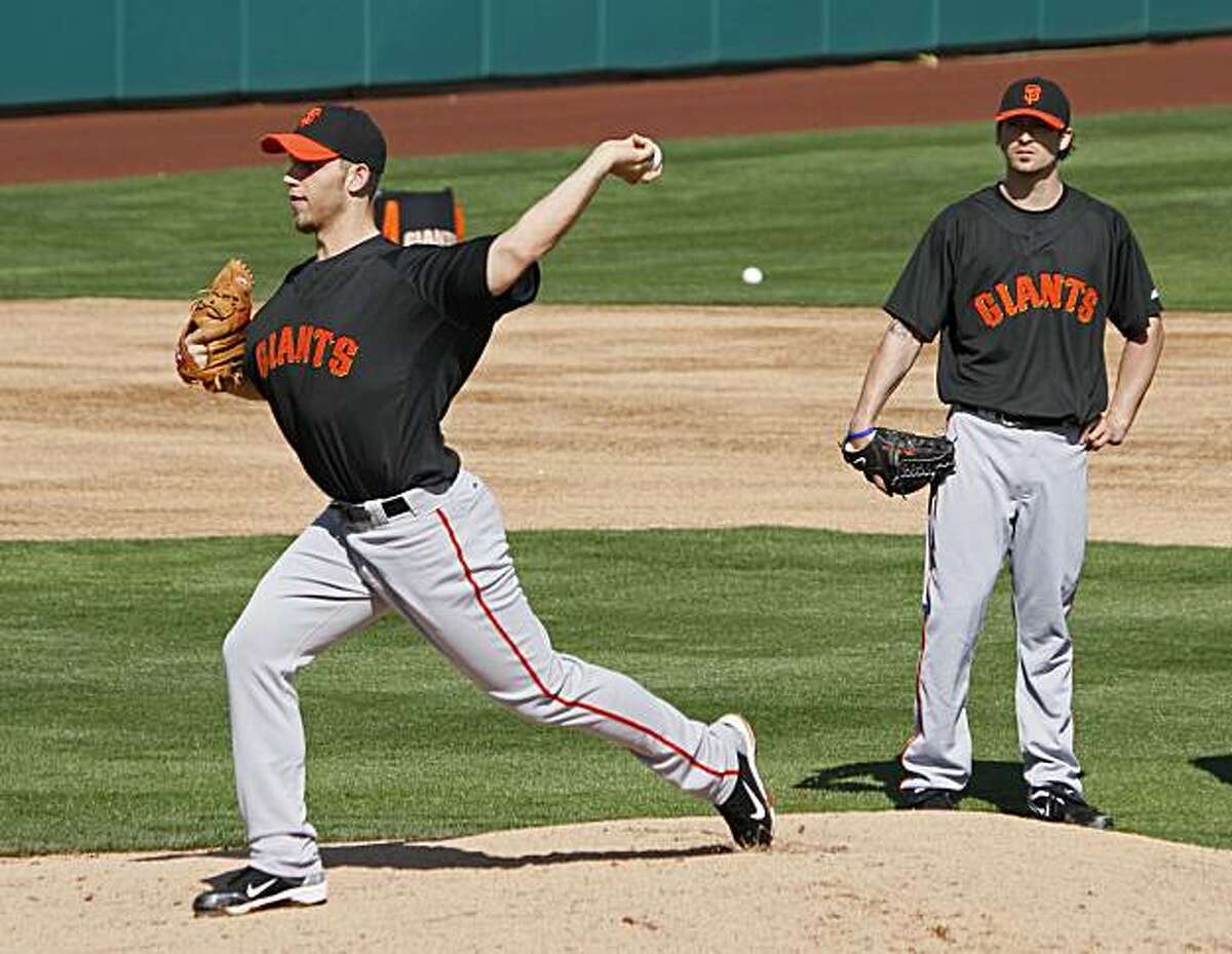 San Francisco Giants pitcher Madison Bumgarner, left, takes part in a drill as pitcher Alex Hinshaw, right, looks on during spring training baseball at Scottsdale Stadiium in Scottsdale, Ariz., Thursday, Feb. 18, 2010.