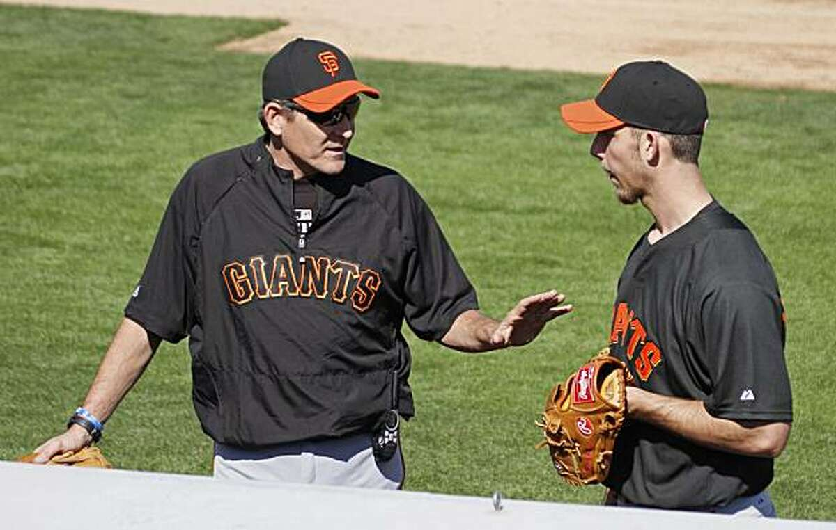 San Francisco Giants pitching coach Dave Righetti, left, talks with pitcher Madison Bumgarner during baseball spring training at Scottsdale Stadium in Scottsdale, Ariz., Thursday, Feb. 18, 2010.