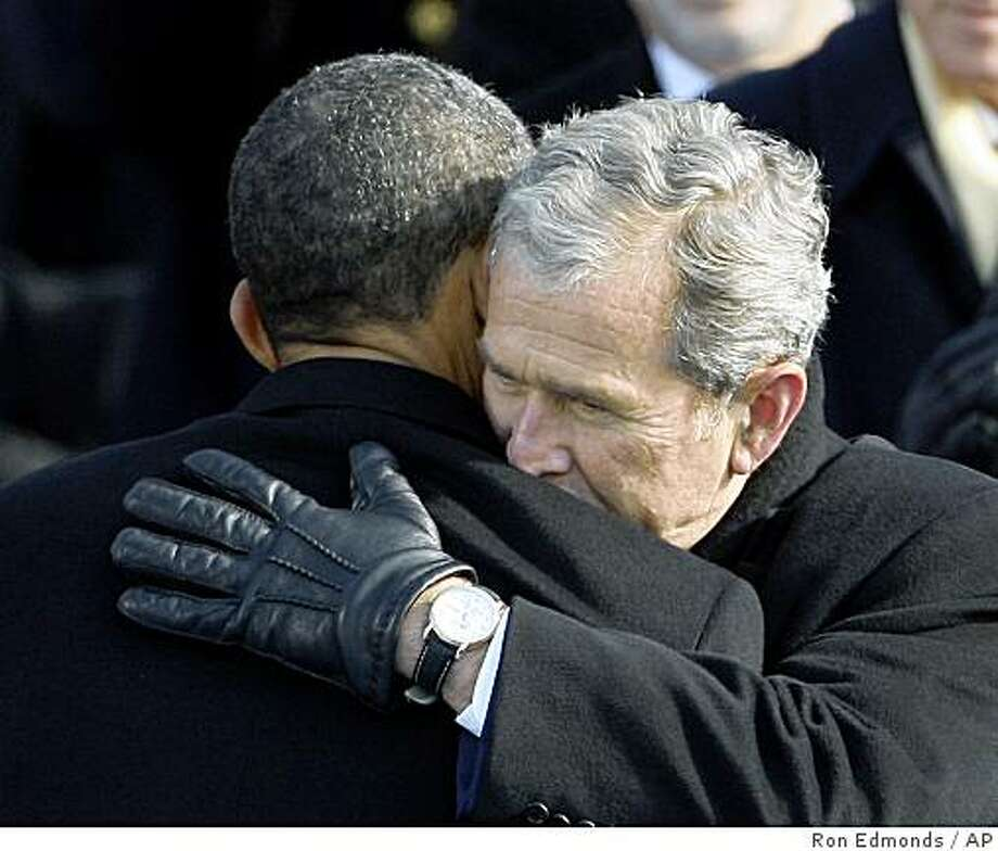 After Barack Obama took the oath of office in 2009, outgoing President George W. Bush, right, hugged him. Their transition, following the economic collapse of 2008, is recognized as one of the United States' smoothest. Photo: Ron Edmonds, AP