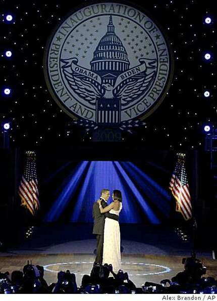 President Barack Obama, left, and first lady Michelle Obama dance together at the Neighborhood Inaug