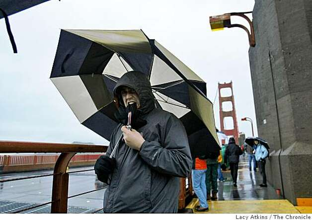 Bob Murtagh waits in the rain and wind for the riders to  cross the Golden Gate Bridge. Photo: Lacy Atkins, The Chronicle