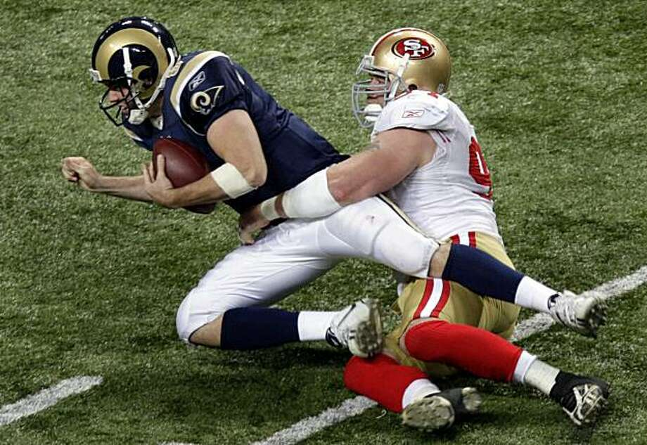 St. Louis Rams quarterback Keith Null, left, is sacked for an 11-yard loss by San Francisco 49ers defensive end Justin Smith during the third quarter Sunday in St. Louis. Photo: Jeff Roberson, AP