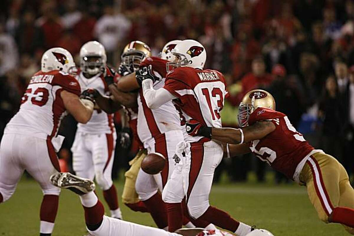 The San Francisco 49ers' Ahmad Brooks grabs Arizona Cardinals quarterback Kurt Warner as he fumbles the ball in the first half of the game on Monday in San Francisco.