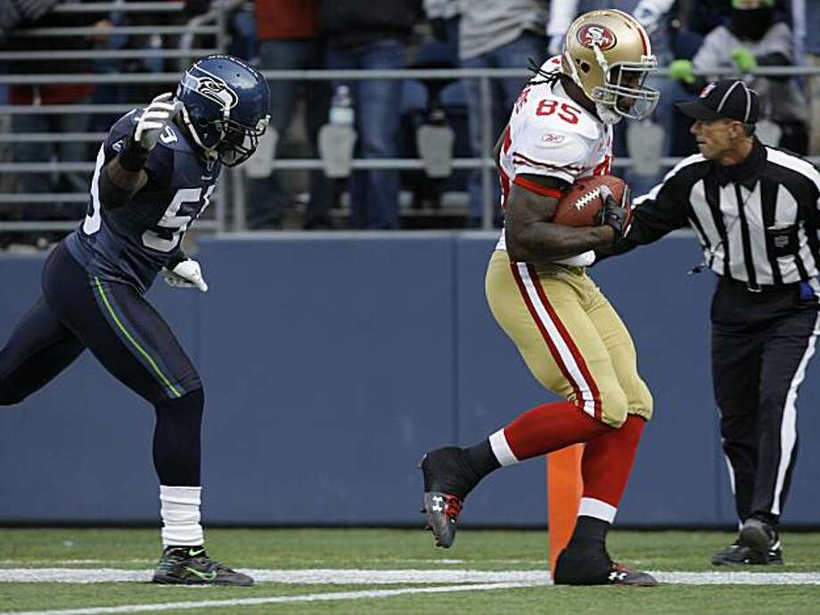 San Francisco 49ers' Vernon Davis scores a touchdown in the first quarter with Seattle Seahawks' Aaron Curry in pursuit Sunday in Seattle. Photo: Elaine Thompson, AP