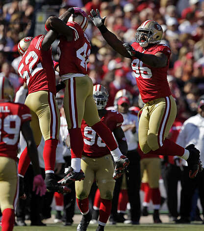 The 49ers' Patrick Willis, Delanie Walker and Kentwan Balmer celebrate after stopping the Rams' Danny Amendola after a three-yard punt return at Candlestick Park in San Francisco on Sunday. Photo: Carlos Avila Gonzalez, The Chronicle
