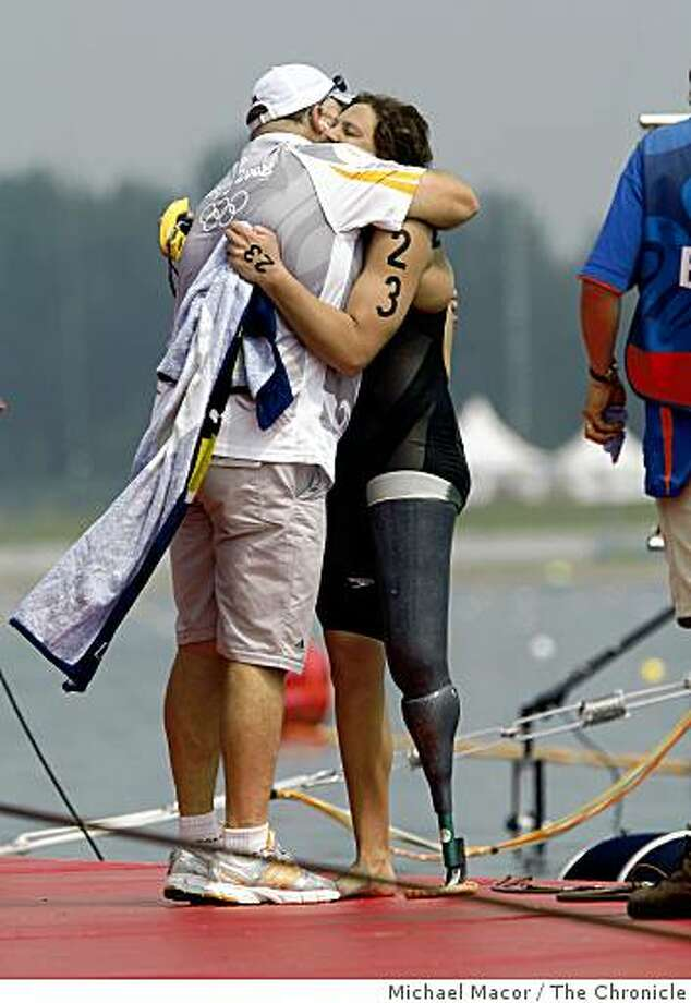 Neville Smith, of South Africa (olympic technician official and friend), hugs Natalie du Toit with her artificial leg after the South African swimmer  finished in 16th place in the women's 10K marathon swim. Photo: Michael Macor, The Chronicle