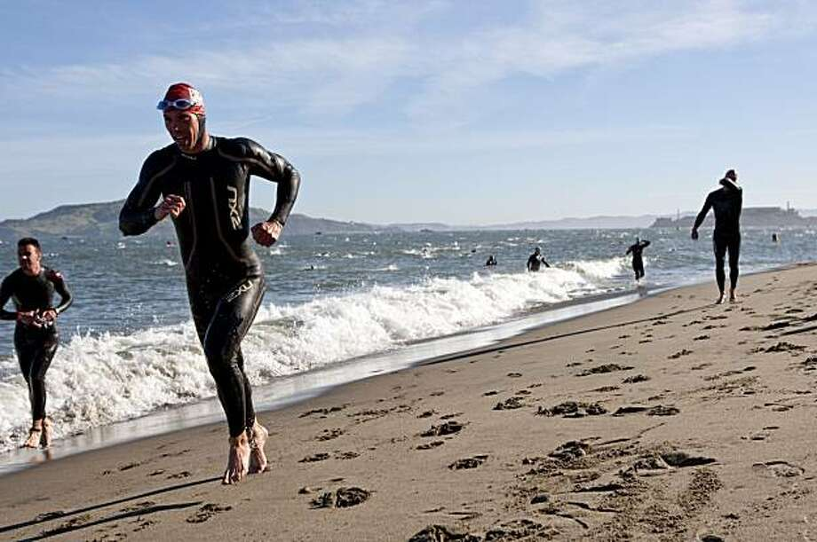 Competitors in the Escape from Alcatraz Triathlon come ashore after finishing the 1.5 mile swim in San Francisco on Sunday. Photo: Laura Morton, Special To The Chronicle