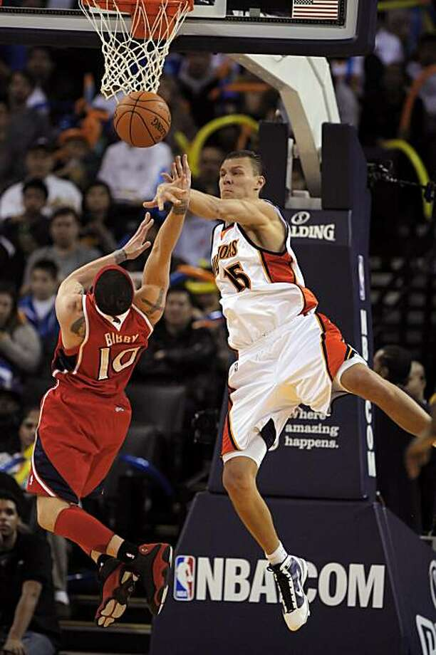 Andris Biedrins blocks a shot by Atlanta's Michael Bibby in the second half of the Warriors' game against the Atlanta Hawks at Oracle Arena in Oakland on Sunday. Photo: Carlos Avila Gonzalez, The Chronicle