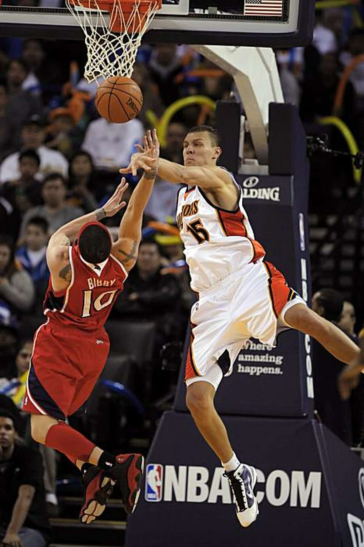 Andris Biedrins blocks a shot by Atlanta's Michael Bibby in the second half of the Warriors' game against the Atlanta Hawks at Oracle Arena in Oakland on Sunday.