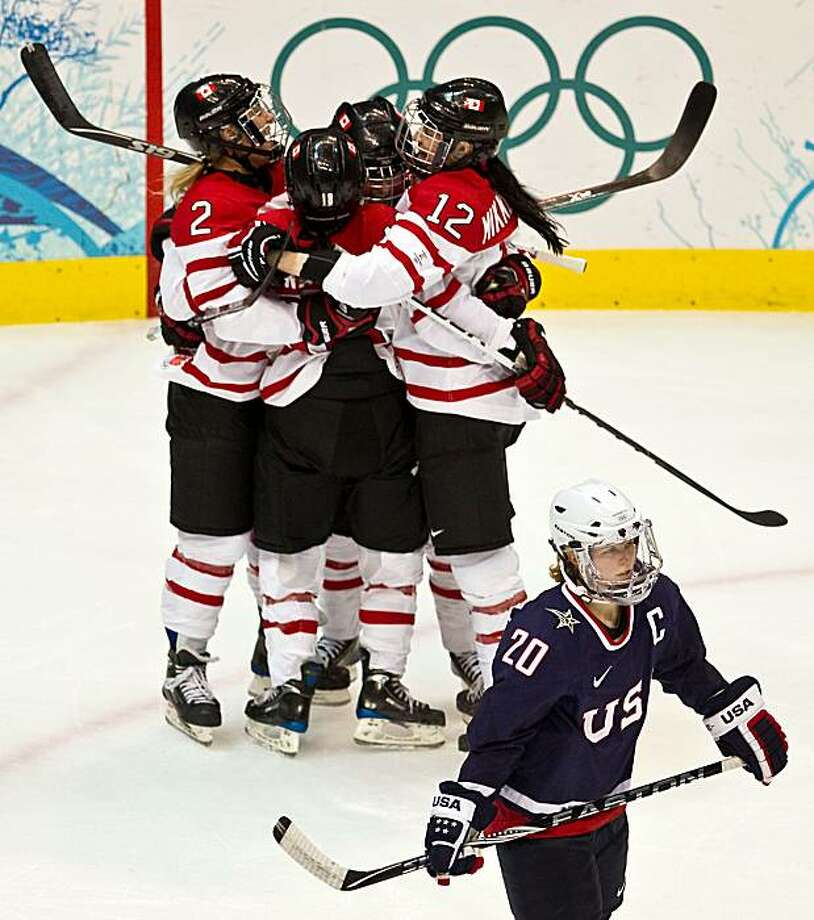 USA's Natalie Darwitz (20) skates away as Team Canada players celebrate a first period goal by Canada's Marie-Philip Poulin in the women's gold medal hockey game at the 2010 Winter Olympics on Thursday, Feb. 25, 2010, in Vancouver.  ( Smiley N. Pool / HoUSA's Natalie Darwitz (20) skates away as Team Canada players celebrate a first period goal by Canada's Marie-Philip Poulin in the women's gold medal hockey game at the 2010 Winter Olympics on Thursday, Feb. 25, 2010, in Vancouver. Photo: Smiley N. Pool, Chronicle Olympic Bureau