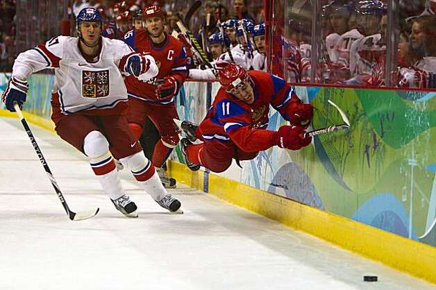 Russia's Evgeny Malkin dives for a puck against the boards as Filip Kuba of the Czech Republic gives chase in men's hockey preliminary round action at the 2010 Winter Olympics on Sunday, Feb. 21, 2010, in Vancouver. ( Smiley N. Pool / Houston Chronicle)Russia's Evgeny Malkin dives for a puck against the boards as Filip Kuba of the Czech Republic gives chase in men's hockey preliminary round action at the 2010 Winter Olympics on Sunday, Feb. 21, 2010, in Vancouver. Photo: Smiley N. Pool, Chronicle Olympic Bureau