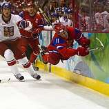 Russia's Evgeny Malkin dives for a puck against the boards as Filip Kuba of the Czech Republic gives chase in men's hockey preliminary round action at the 2010 Winter Olympics on Sunday, Feb. 21, 2010, in Vancouver. ( Smiley N. Pool / Houston Chronicle)Russia's Evgeny Malkin dives for a puck against the boards as Filip Kuba of the Czech Republic gives chase in men's hockey preliminary round action at the 2010 Winter Olympics on Sunday, Feb. 21, 2010, in Vancouver.