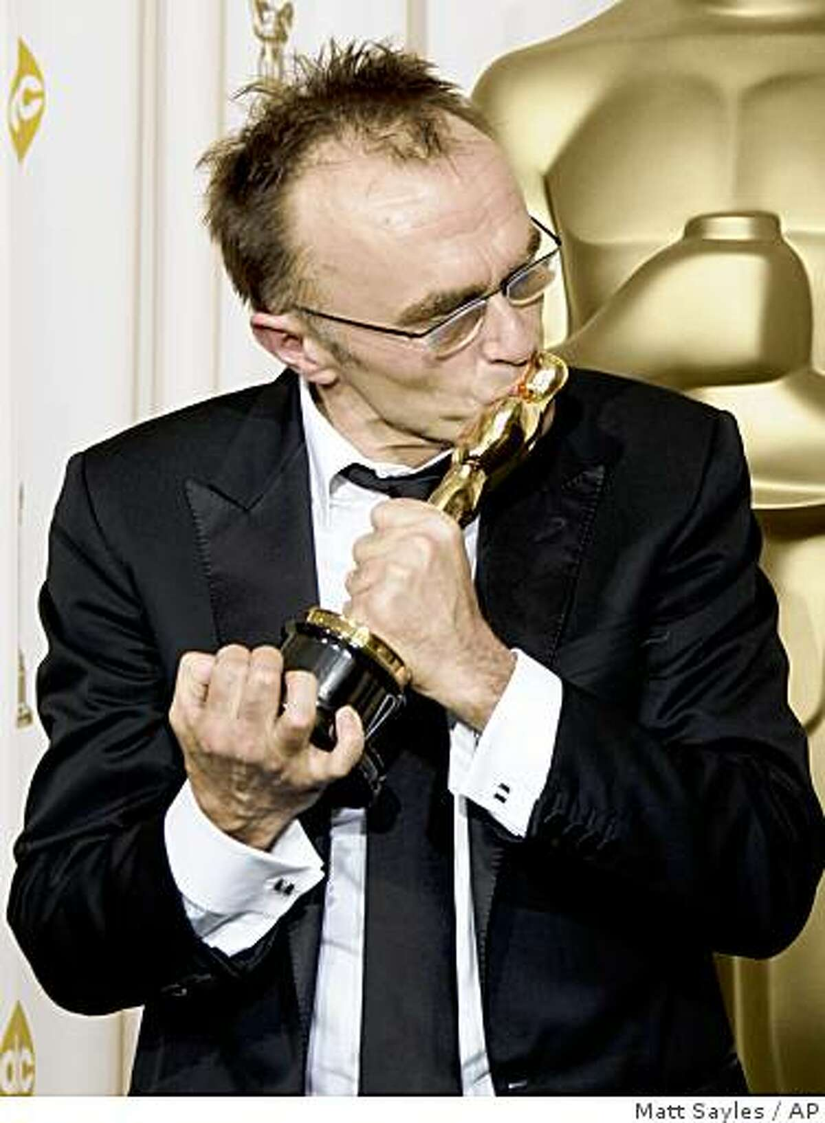 British director Danny Boyle kisses the Oscar for best director for his work on