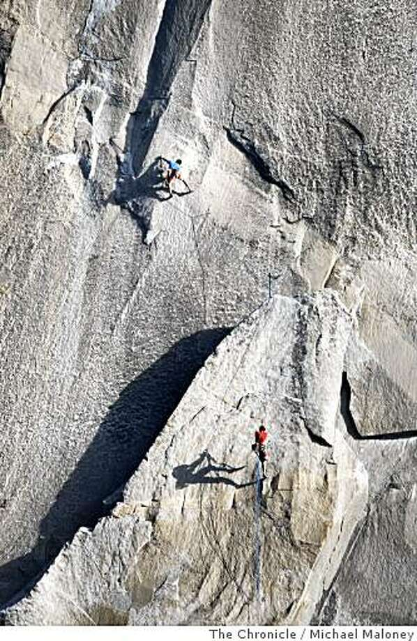 Speed climbers Yuji Hirayama, top, of Japan and Hans Florine, below of Lafayette, Calif., cast long shadows on the granite wall near Texas Flake in an attempt at a new record of climbing the Nose route of El Capitan in Yosemite National Park on June 29, 2008. Their time was 2 hours, 47 minutes, just shy of the record of 2 hours and 45 minutes.Photo by Michael Maloney / The Chronicle Photo: Michael Maloney, The Chronicle