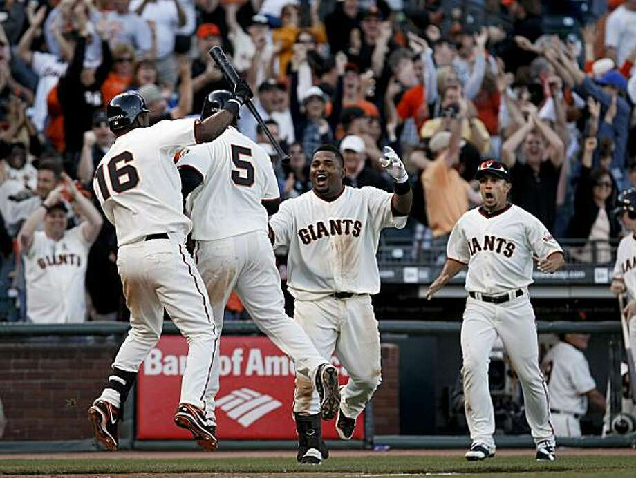 Edgar Renteria celebrates with Juan Uribe, who scored on Aaron Rowand's single in the 13th inning to win the Giants' home opener against the Braves on Friday. Pablo Sandoval and Andre Torres join in. Photo: Michael Macor, The Chronicle