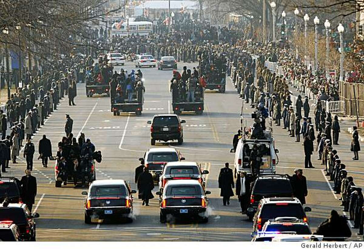 Secret Service agents walk alongside President Barack Obama's limousine as they go from Capitol Hill to The White House during the Inaugural Parade in Washington, Tuesday, Jan. 20, 2009.