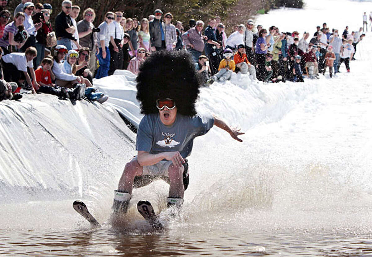 A competitor attempts to skim across a man-made pond on skis, Saturday, April 3, 2010, at Saddlleback Ski Area in Rangeley, Maine. Nearly 100 competitors took part in the annual end-of-the-season celebration.