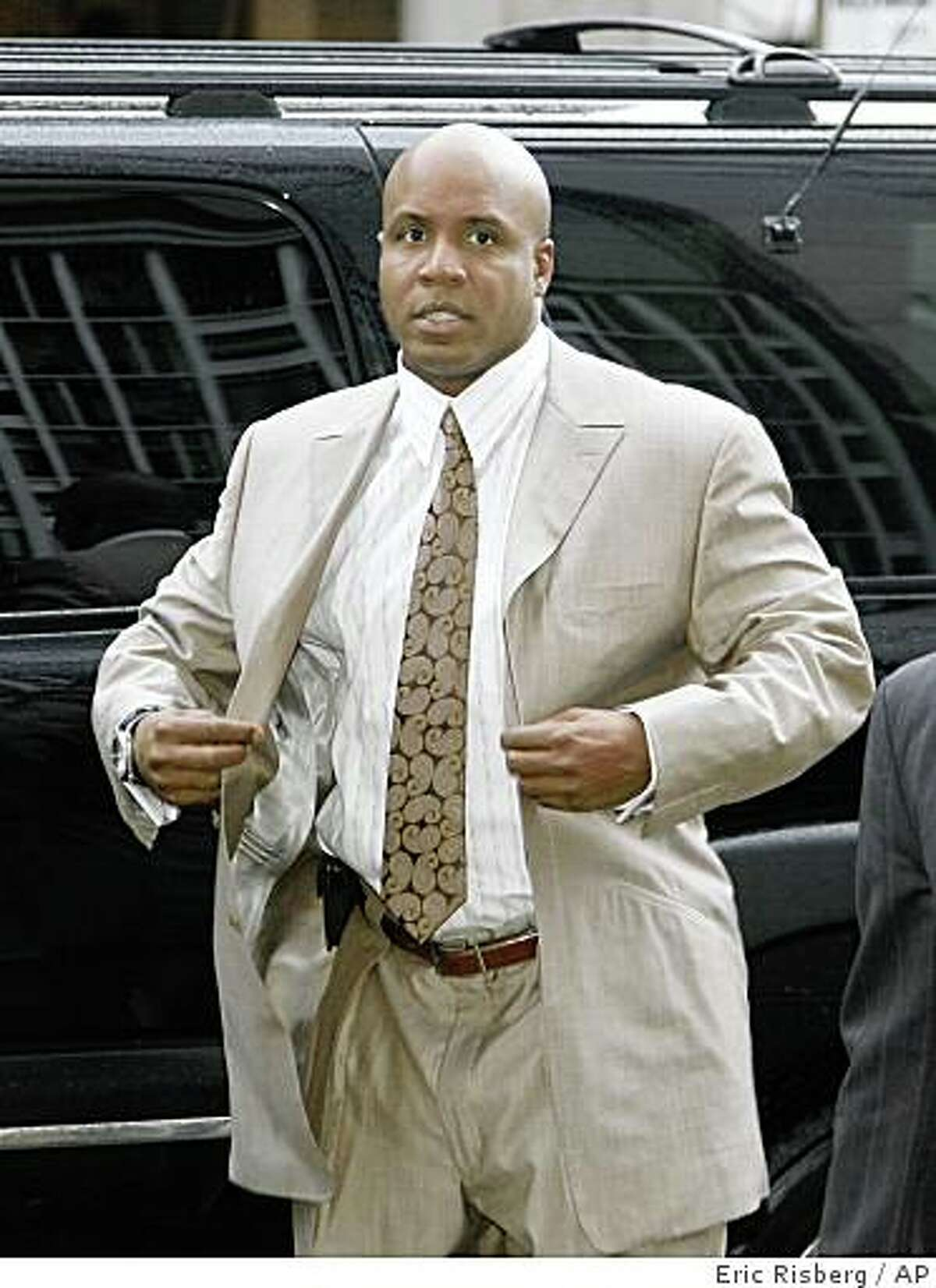 Barry Bonds buttons his jacket after arriving to enter a plea at the Federal building in San Francisco, Thursday, Feb. 5, 2009. Bonds' trial for perjury and obstruction of justice charges begins next month.