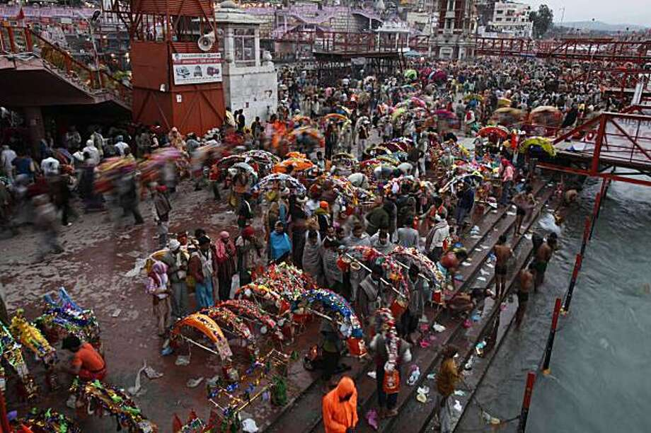 Kanwarias prepare to take holy dip in the River Ganges as part of monthslong Hindu festival Kumbh Mela, in Haridwar, India, Monday, Feb. 8, 2010. Kanwarias are young men performing a ritual pilgrimage in which they walk, sometimes hundreds of kilometers (miles), to the Ganges River to take its sacred waters back to Hindu temples in their hometowns. Photo: Rajesh Kumar Singh, AP