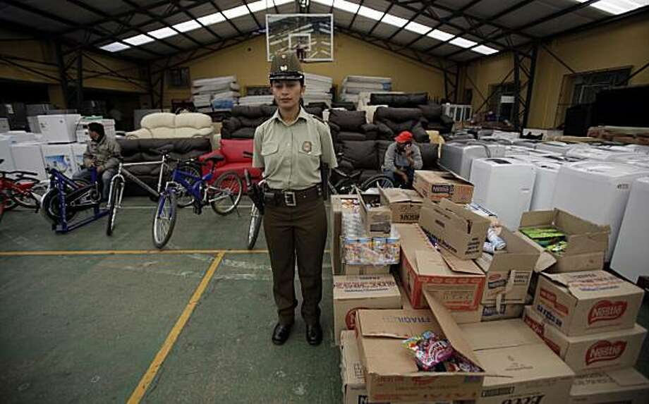 A police officer stands in front of hundreds of items either returned by looters or recovered by the police at a police station in Concepcion, Chile, Sunday March 7, 2010. Looting started after an 8.8-magnitude earthquake struck central Chile last Feb. 27, causing widespread damage. Photo: Natacha Pisarenko, AP