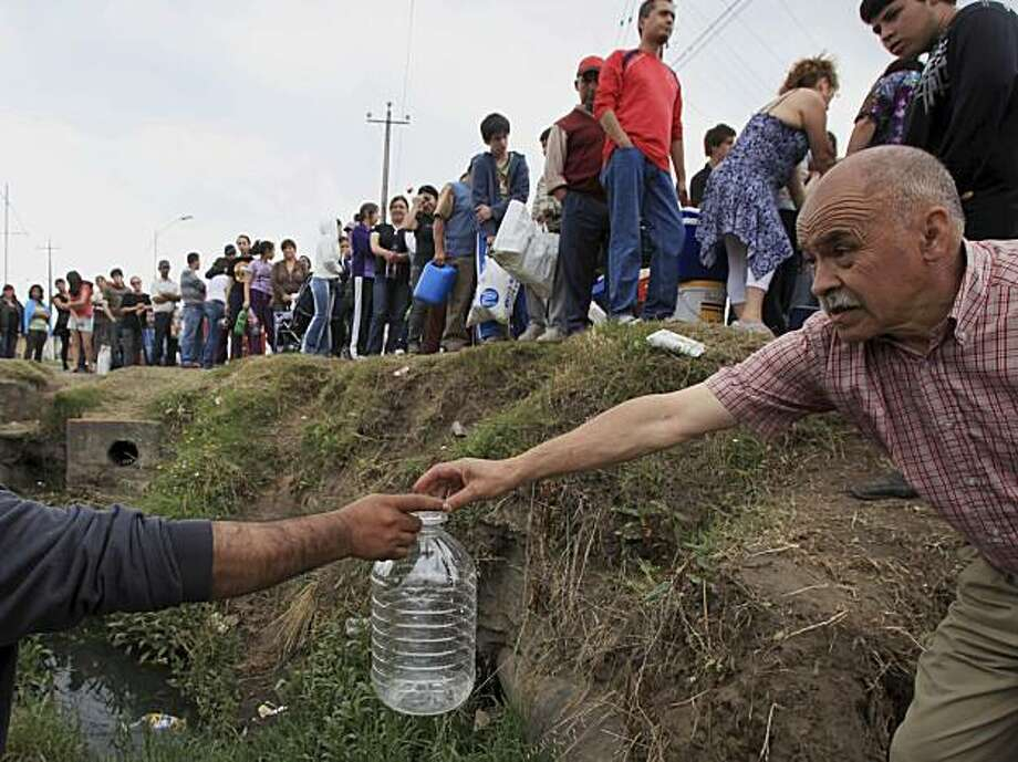 A man receives an empty bottle to fill it with water from a damaged main in Concepcion, Chile, Tuesday, March 2, 2010. Central Chile was hit by a powerful earthquake Feb. 27. Photo: Ricardo Mazalan, AP