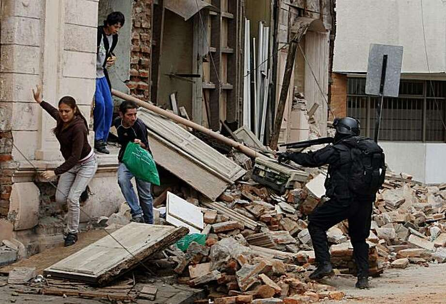 A police officer aims at people that were looting goods from a store damaged during the magnitude-8.8 earthquake in Talcahuano, Chile, Tuesday, March 2, 2010. Photo: Ricardo Mazalan, AP
