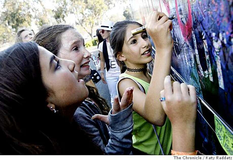 Danielle Chetrit, 11, from Redwood City, and Megan Colford, 11, from Los Altos, second from left, wait impatiently for their friend Maria Khouri-Haddad, 11, right, who flew all the way from Dubai for this concert, to sign the side of the Jonas Brothers' tour bus, outside the Shoreline Amphitheater where the Jonas Brothers will appear, in Mt. View, Calif.  on Tuesday,  July 15, 2008.Photo by Katy Raddatz / The Chronicle Photo: Katy Raddatz, The Chronicle