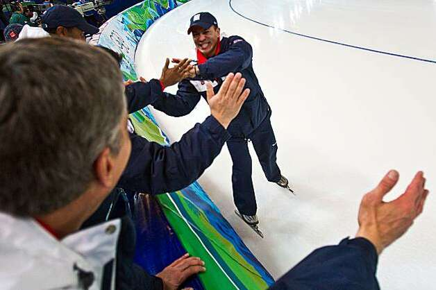 USA coach Derek Parra celebrates with the team delegation, including team doctor, and speedskating icon, Eric Heiden, left, after an upset win over the Netherlands during the men's speed skating team pursuit semi finals at the 2010 Winter Olympics on Friday, Feb. 26, 2010, in Vancouver.  The USA will now skate for the gold medal on Saturday. ( Smiley N. Pool / Houston Chronicle) Photo: Smiley N. Pool, Chronicle Olympic Bureau