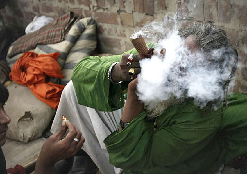 A Pakistani devotee smokes hashish during the annual festival of the 14th century Sufi saint Mian Mir in Lahore, Pakistan, Monday, Feb. 22, 2010.