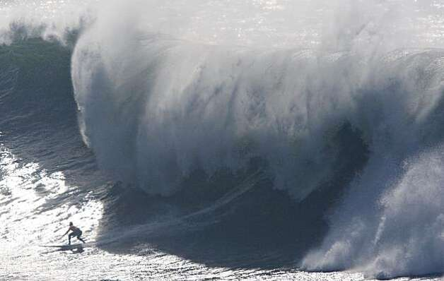 A surfer races under the falling lip of crashing waves during the finals of the Mavericks Surf Contest in Half Moon Bay, Calif. on Saturday, Feb. 13, 2010. Photo: Adam Lau, The Chronicle