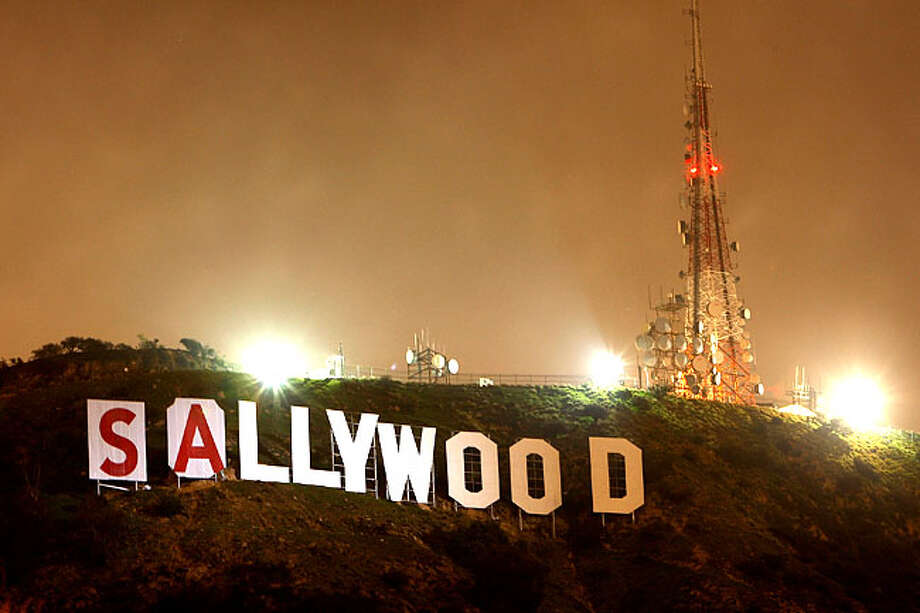 The light of a police helicopter illuminates the work of activists after they stopped work for the night on covering up the iconic 450-foot-long Hollywood sign during an effort to prevent the building of houses there on February 11, 2010 in Los Angeles, California. The message will read Save the Peak. The Trust for Public Land is draping the sign as it campaigns to raise enough funds to buy Cahuenga Peak and stop developers from purchasing the 138-acre parcel to build mansions around the Hollywood sign. A group of Chicago investors who bought the property from the estate of aircraft titan Howard Hughes in 2002 announced that they plan to subdivide the peak into luxury home sites. The land trust has raised about half the $ Photo: David McNew, Getty Images